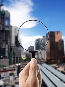 44926999 - magnifying glass and cityscape in focus, business vision